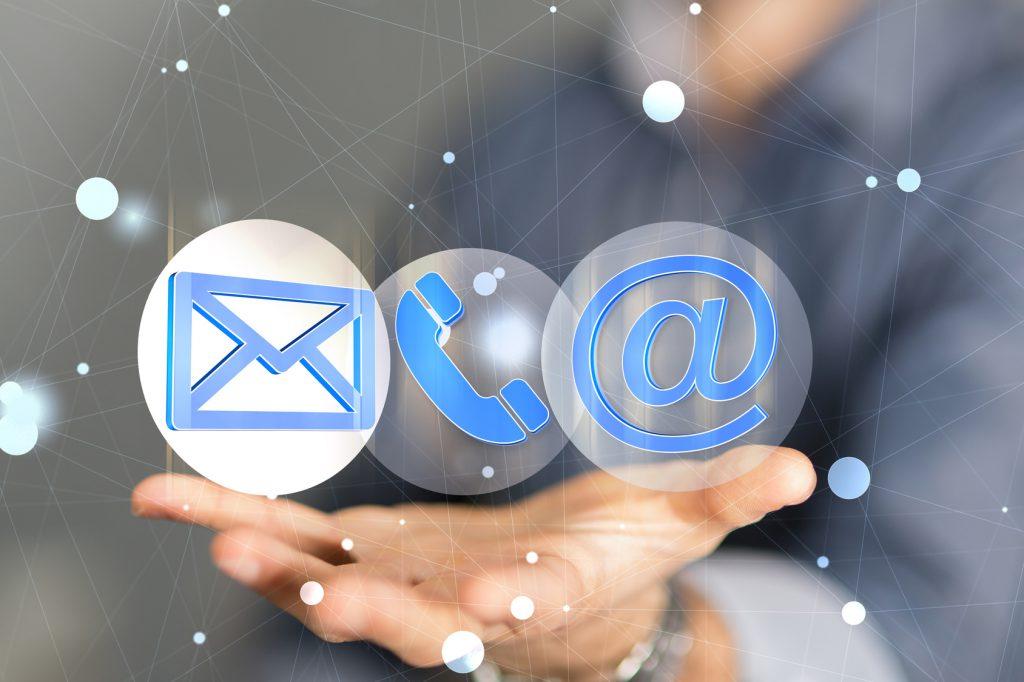 nico europe unternehmen company kontakt contact symbole e-mail, telefonhörer und @ schweben über geöffneter hand, symbolisches netzwerk im hintergrund