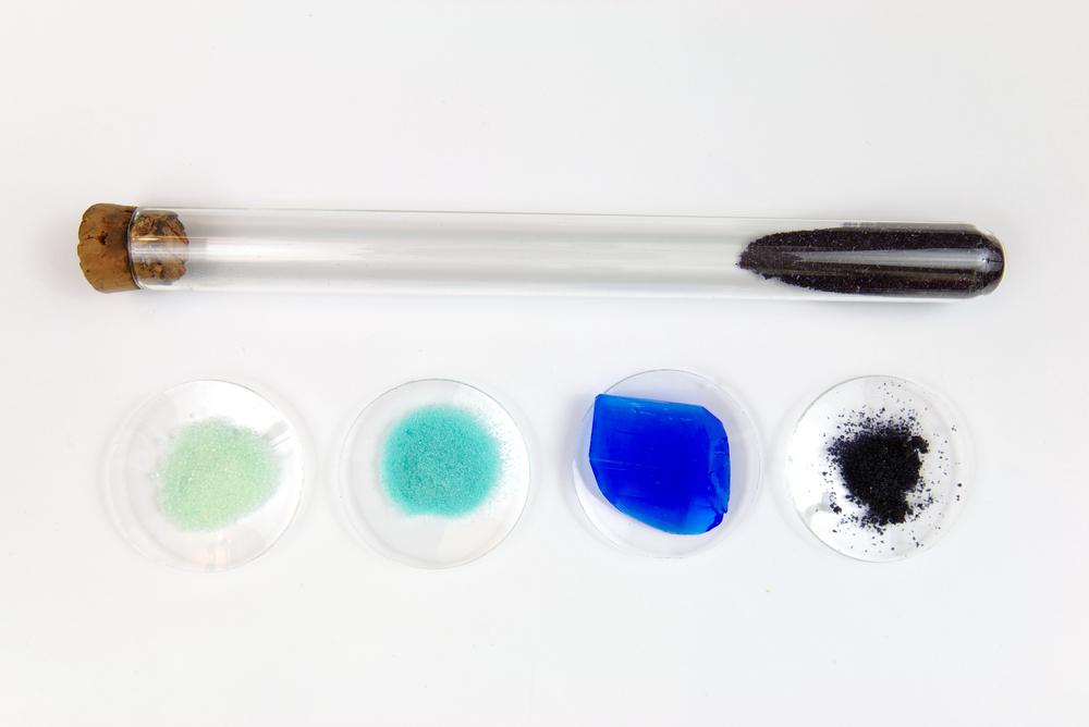 nico europe info chemie türkise, grüne, schwarze salze, blaue mineralien in petrischalen, daneben verkorktes reagenzgläschen mit schießpulver