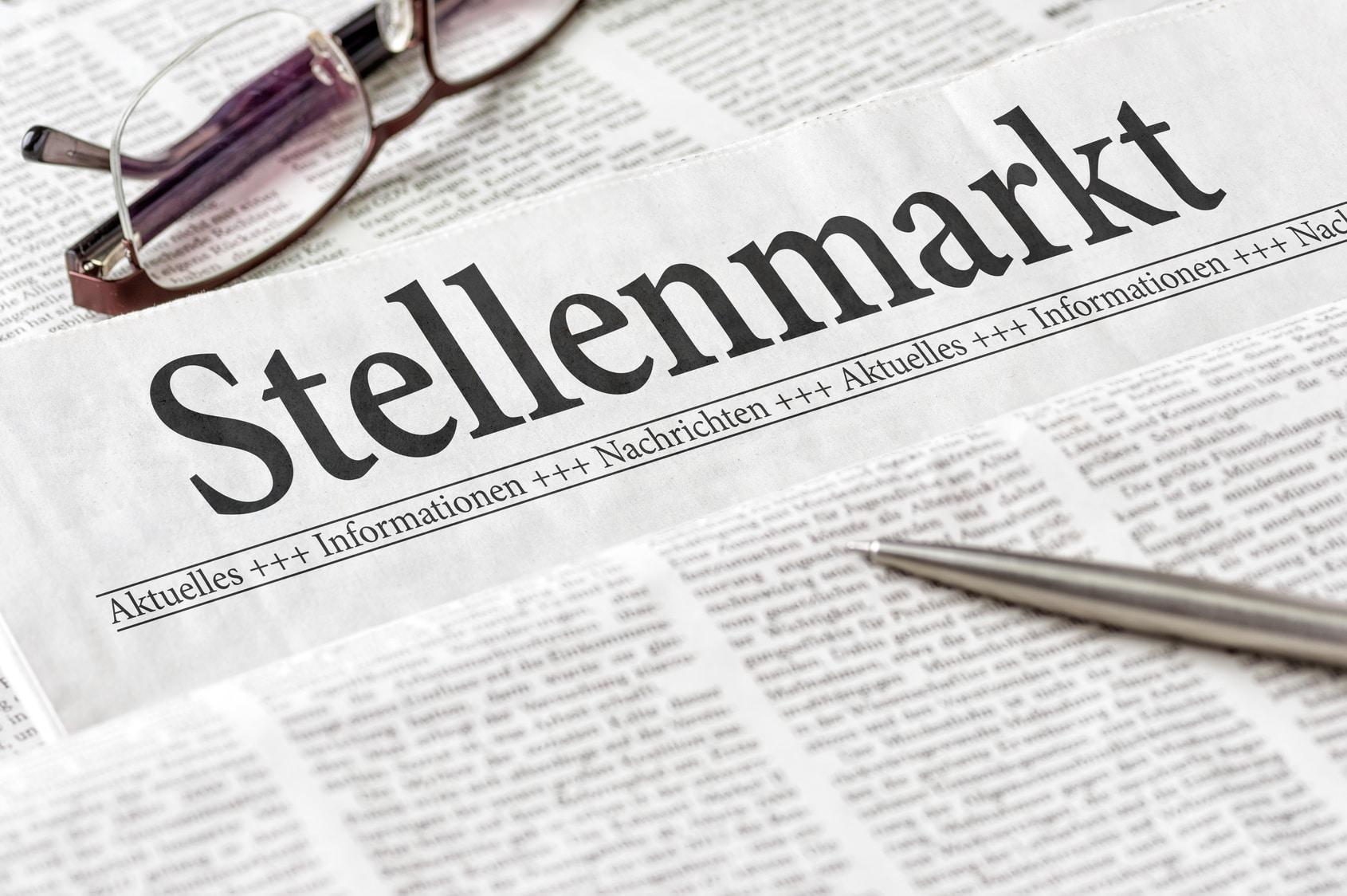 nico europe unternehmen karriere career brille und kugeslschreiber liegen auf zeitungen mit headline stellenmarkt