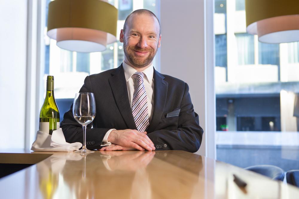 nico europe b2b hotel & gastronomie hotel & catering mann im anzug sitzt lächelnd an bar mit weinflasche und gefülltem weinglas, im hintergrund lampen und fenster mit blick auf hotelgebäude