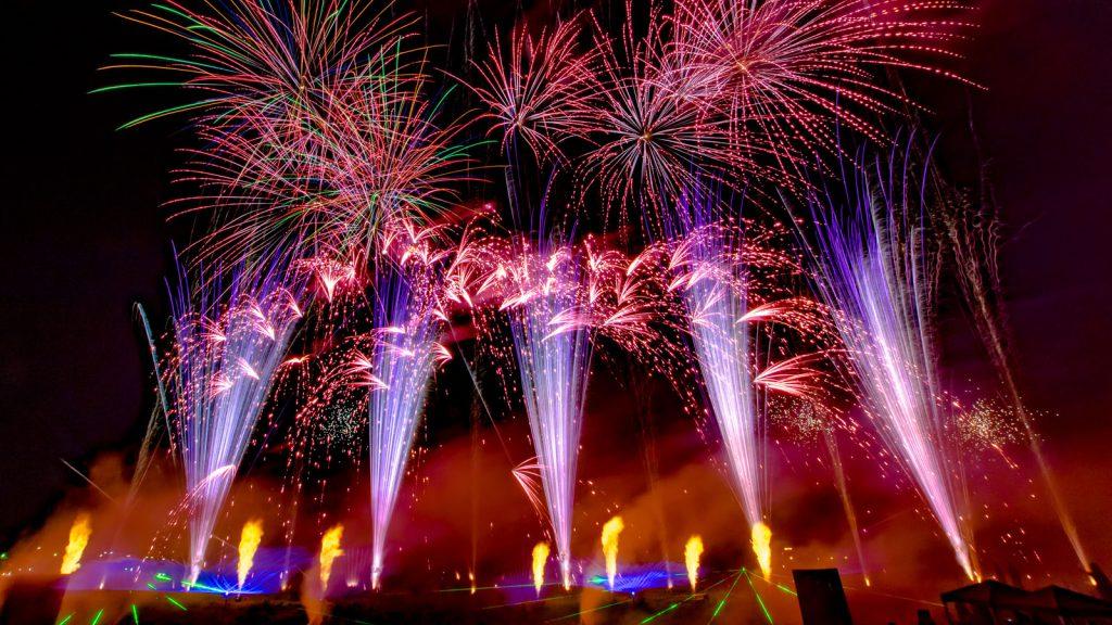 nico europe unternehmen company hoffest 2016 summer party 2016 flammen- und lasereffekte am boden, lila aufstiege zu rosa palmeneffekten, darüber viele bunte blink- und sterneffekte in grün, rot, blau, pink, orange
