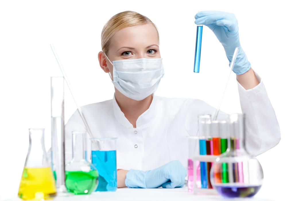 nico europe info chemie junge frau im weißen kittel mit mundschutz und handschuhen hält reagenzgläschen mit blauer flüssigkeit hoch, vor ihr weitere gläser und kolben mit diversen bunten flüssigkeiten und pipetten