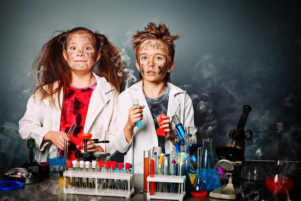 nico europe info chemie maedchen und junge im labor, experiment fehlgeschlagen, rauchschwaden fleckige Kleidung, überraschte und leicht geschwaerzte gesichter und wuschelige haare