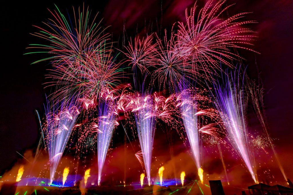 nico europe feuerwerke hoffest blaue aufstiege zu roten blinkeffekten, darüber rot-grüne sterne, am boden flammen- und grüne lasereffekte