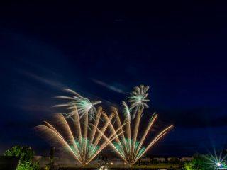 nico europe feuerwerke potsdamer feuerwerkersinfonie zwei gefächerte aufstiege in gold mit grünen sternen, darüber zwei palmeneffekte mit grünem zentrum
