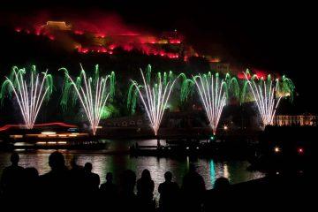 nico europe feuerwerke rhein in flammen zuschauer auf schiff bestaunen grün-silberne fächereffekte am boden und darüber rot beleuchtetes schloss
