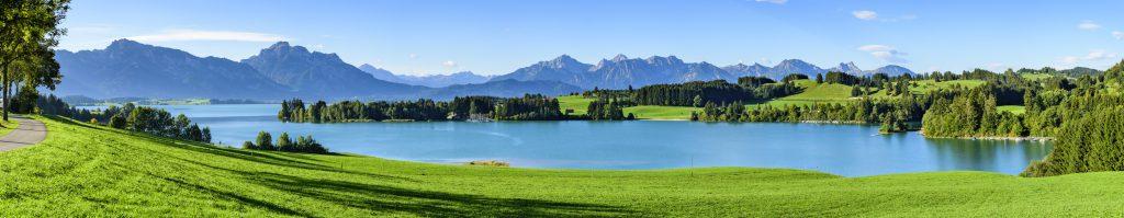 nico europe info umwelt environment aussicht über saftige grüne wiesen bei sonnenschein zu einem großen see, im hintergrund bäume, gebirge und wolken