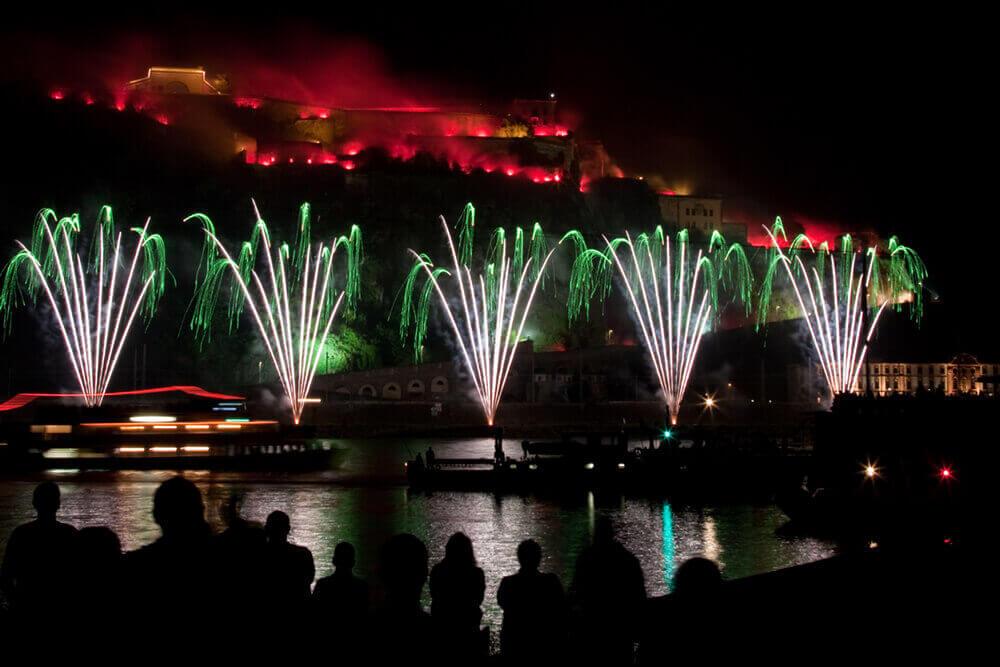 nico europe feuerwerke fireworks rhein in flammen rhine in flames fünf gefächerte wasserfalleffekte am boden, im hintergrund rot beleutchtete burg