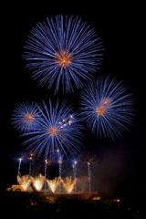 nico europe feuerwerke fireworks rhein in flammen rhine in flames viele goldene fächeraufstiege in einer reihe, daüber blaue kugelförmige effekte mit goldenem zentrum