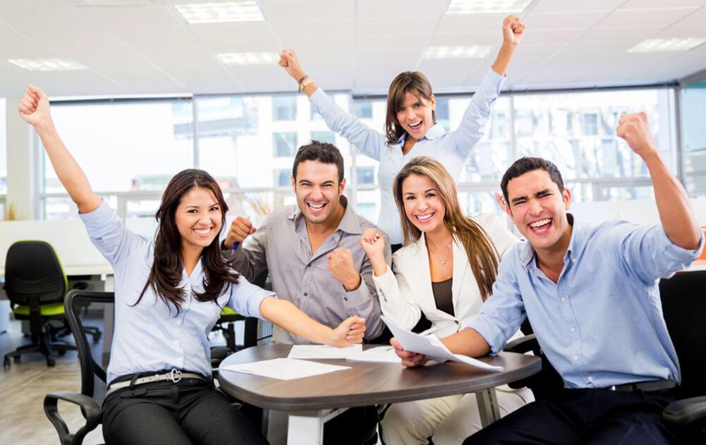 nico europe unternehmen company team junge motivierte jubelnde mitarbeiter an tisch sitzend und fäuste in die Luft reckend