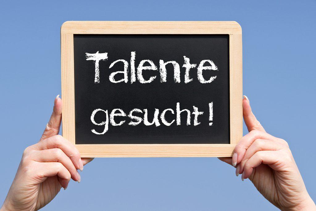 """nico europe unternehmen company karriere career schiefertafel mit holzrahmen, aufschrift """"Talente gesucht"""", wird von zwei weiblichen Händen hochgehalten"""