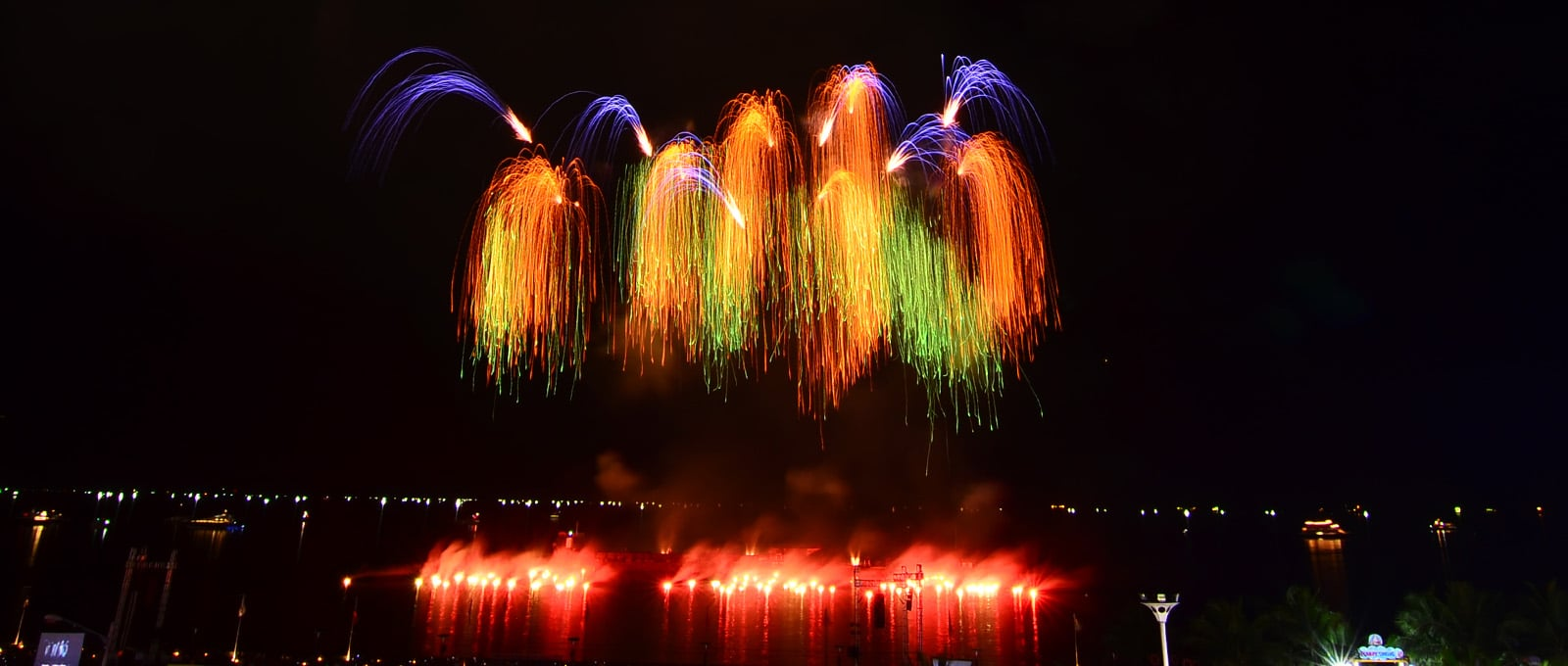 nico europe feuerwerke 8. philippine international pyromusical competition manila orange, grüne und lila trauerweideneffekte über roten lichtern auf dem Meer